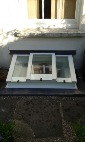 Basement window made with wood from a church in Totterdown that was converted into flats